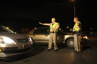 Metro Police officers Chris Same and Steve Hutchason, right, stop a vehicle while looking for impaired drivers Saturday evening at a DUI checkpoint on Rainbow Boulevard north of Cheyenne Avenue.
