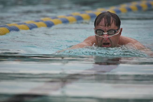 Walt Muir gets some exercise swimming the breaststroke while his grandchildren play in the water Saturday during closing day at Boulder City Pool.