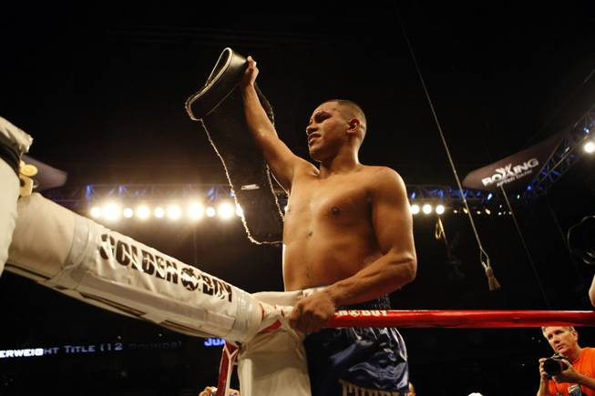 Juan Diaz of Houston holds up the NABO Junior Welterweight title belt after he defeated Paulie Malignaggi in a decision in 12 rounds on Aug. 22, 2009, in Houston.