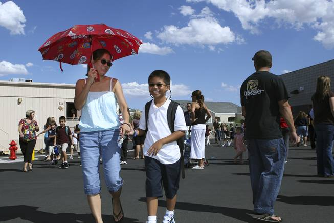 Third grader Shane Collado laughs with his mom, Mary Ann, on the playground after the first day of classes Monday at Steve Schorr Elementary School in Henderson.