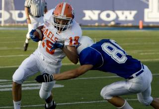 Bishop Gorman wide receiver Michael McRea takes a hit from Dixie cornerback Tanner Mitchell Friday in St. George, Utah.