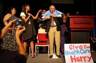 Sen. Harry Reid receives a medical scrub shirt signed by SEIU members at the close of a Nevada State Democratic Party health care rally in the UNLV student union in Las Vegas on Monday night, Aug. 31, 2009.
