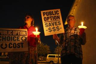 Mary Venable, who is uninsurable because of a pre-existing condition, joins Rudi Kraft in holding signs and candles in support of health care reform during a candlelight vigil Sept. 2 in Boulder City.