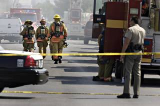 Firefighters respond to the site of a fire where one person was shot to death and a Metro Police officer was wounded in the arm in Las Vegas on Wednesday, Sept. 2, 2009.