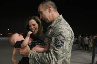 Master Sgt. Shaun Davis holds his 5-month-old son, Tommy, as his wife, Kristy, sheds tears beside them during a welcome-home celebration Sunday night at Nellis Air Force Base.