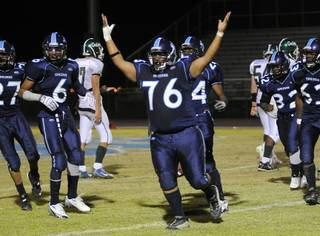 Pioneers defensive lineman Nicolas Rogers (76) celebrates after making an interception in the second half against Green Valley at Canyon Springs High School on Friday night.