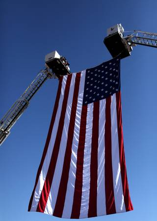 An flag is raised by two cranes during a ceremony Friday at the Clark County Government Center Amphitheater to commemorate the eighth anniversary of the Sept. 11, 2001, terrorist attacks in New York, Washington, D.C., and Pennsylvania.