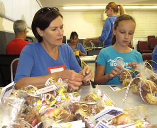 Proud Blue Star Mother Shannon Scaletta and her granddaughter, Sofie, wrap cookies to be delivered on Sept. 11.
