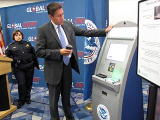 Carlos Martel, Los Angeles area port director for the U.S. Customs and Border Protection, demonstrates how to use the new Global Entry kiosk at McCarran International Airport on Wednesday.