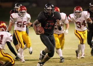 Hassan Henderson of Las Vegas runs past the Del Sol line for a huge gain during the Thursday night game against Del Sol at Las Vegas High. Del Sol won a close one 33-28.