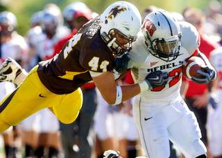 Wyoming defender Josh Biezuns (44) tackles UNLV running back Channing Trotter during Wyoming's 30-27 win Saturday in Laramie, Wyo.