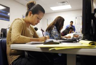 Eva Leticia, 23, works on math problems during a free class Tuesday, Sept. 22, 2009. A school district program with private foundation money uses Mexican government-supplied materials to teach functionally illiterate parents to read and write in Spanish.