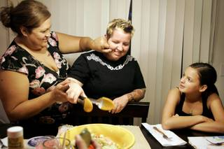 Carline Banegas, left, playfully pinches her partner Jodie Dearborn's cheek during dinner as their daughter Dakota Banegas, 13, waits for her salad in their Las Vegas home Monday, Sept. 28, 2009.