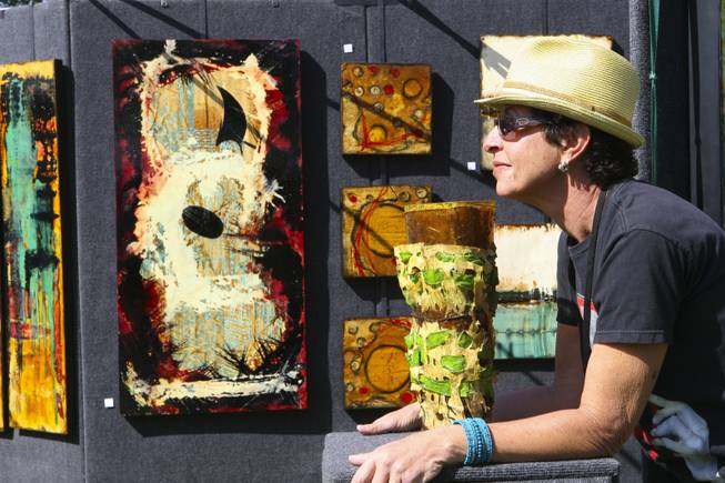 Artist Angela Alvarez relaxes in the sunshine while hoping to sell one of her two-dimensional mixed media pieces on steel Sunday during the 47th Annual Art in the Park in Boulder City.