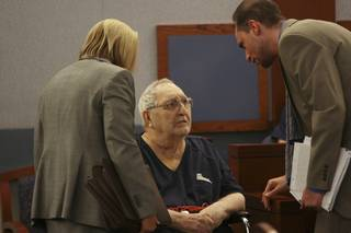 Deputy public defenders Kristine Kuzemka and Dan Silverstein, right, speak with Joseph Woods, 86, during a hearing before Justice of the Peace Nancy Oesterle on Oct. 8 at the Regional Justice Center.
