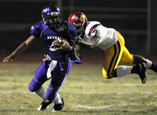 Skyhawks quarterback Trenten Tipton attempts unsucessfully to evade Dragons tackler Dezerick Reed, and is sacked on the play during a game at Silverado High on Friday night.