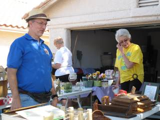 Tall Club members John Morath and Regena Uppleger look at some of the items at the club's semiannual garage sale that raises money for its Tall Awareness scholarship.