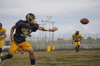 Senior quarterback Ross Lamarca pitches the ball while running offensive drills during practice at Boulder City High.