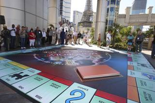 Finalists and passersby gather around the 25-by-25 foot big Monopoly board in preparation for the start of the Monopoly