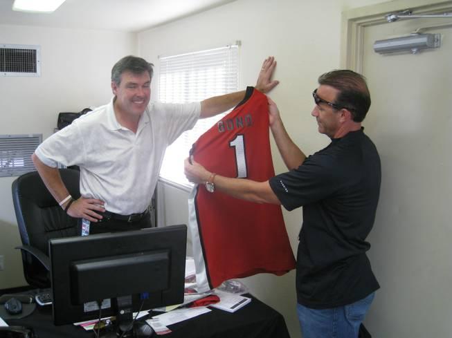 Daren Libonati shows off a new UNLV Runnin' Rebels jersey to Live Nation exec Craig Evans in the hope that Bono might wear it onstage (he didn't).