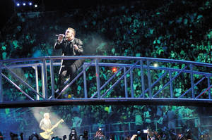 Bono, the lead singer of U2, performs from a bridge over the crowd Friday at Sam Boyd Stadium as part of the band's 360 Tour.