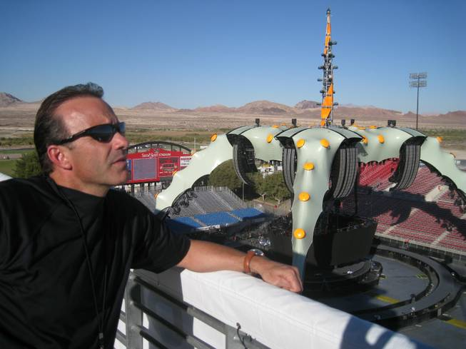 "Daren Libonati, atop Sam Boyd Stadium, ""The Claw"" in the background."