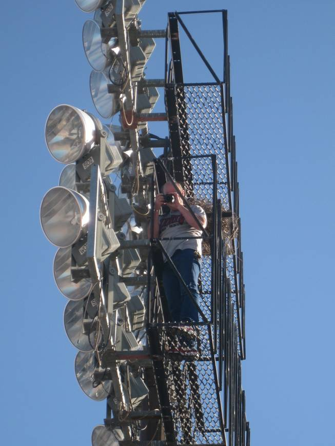 Sam Boyd Stadium Operations Director Jeff Chalfant scales a 150-foot light standard for some unique photographic perspective.
