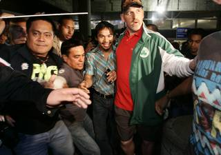 Filipino boxer Manny Pacquiao is greeted by fans as he arrives at Los Angeles International Airport Saturday, Oct. 24.