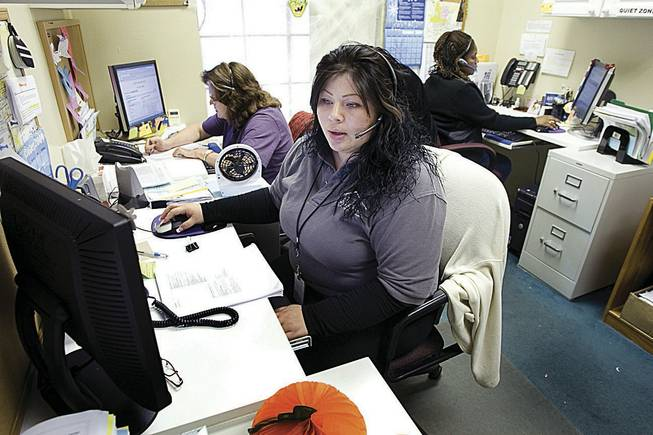 Giselle Sanchez, center, Carolyn Graham, left, and Belinda Brooks are among 13 operators statewide who field calls to Nevada's 2-1-1 help line, which tries to match people in need with public services.