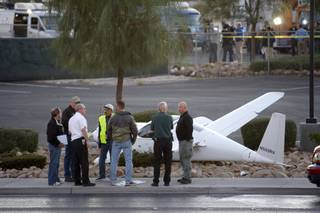 Investigators look over an experimental plane after the pilot made a forced landing on Rancho Drive near Texas Station on Friday, Oct. 30, 2009.