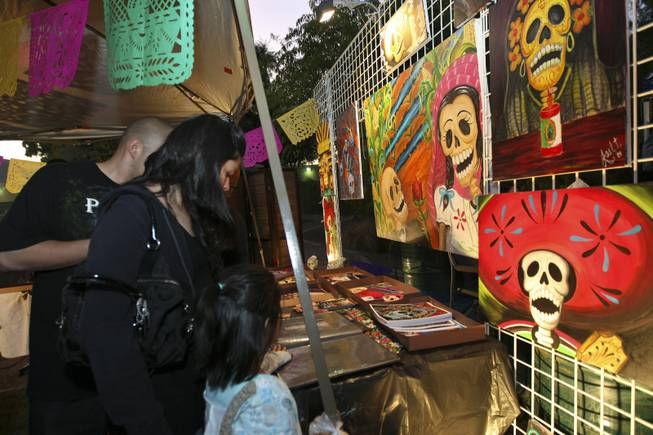 From left, Alex Zamora, Alicia and Priscilla Vasquez, 5, admire the oil and acrylic paintings by Joel Tirado for sale during the annual Life in Death: Day of the Dead Festival Sunday night at the Winchester Cultural Center and Park.