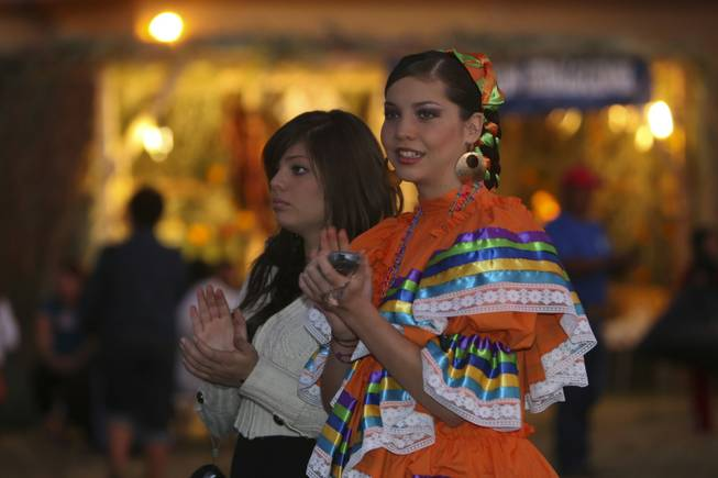Wearing an authentic Mexican dress, Nancy Paz, 15, and her sister, Blanca, 17, applaud a Mexican dance troup performing Sunday night at the annual Life in Death: Day of the Dead Festival at the Winchester Cultural Center and Park.