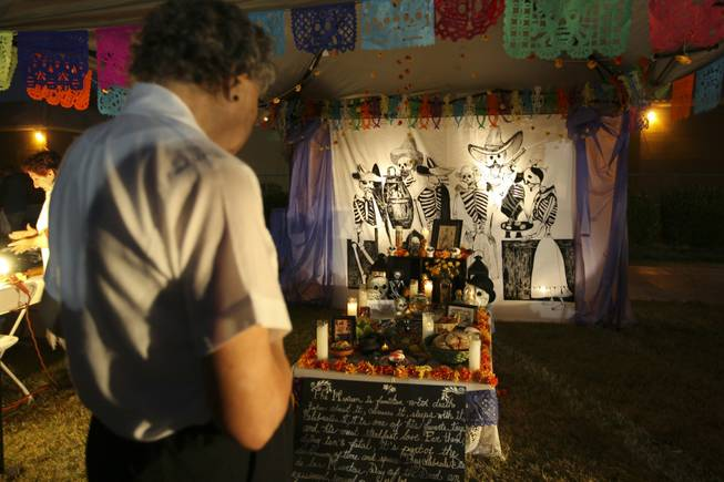 Rosaura Sanchez pays respect at the altar in memory of Jose Guadalupe Posada, a Mexican engraver, illustrator and artist, at the annual Life in Death: Day of the Dead Festival Sunday night at the Winchester Cultural Center and Park.