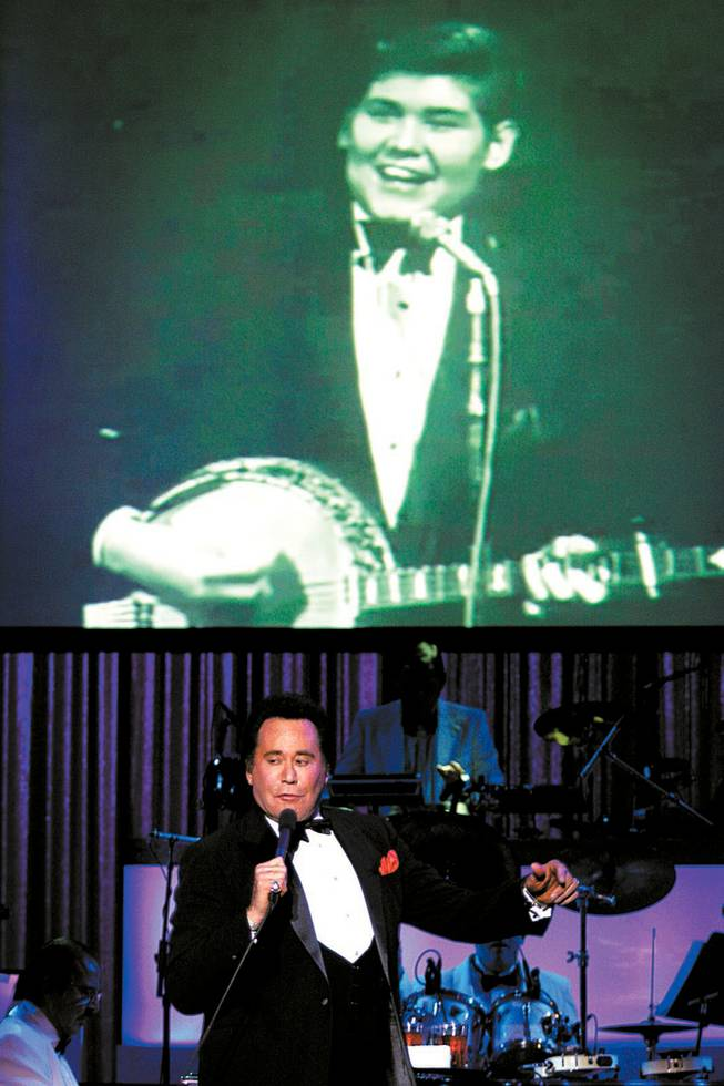 "Wayne Newton performs as a photo of him as a young man flashes on the screen during the opening night performance Wednesday of ""Once Before I Go"" at the Tropicana. The show traces Netwon's career and has him singing duets with the likes of Sammy Davis Jr. and Dean Martin, who appear on video screens."