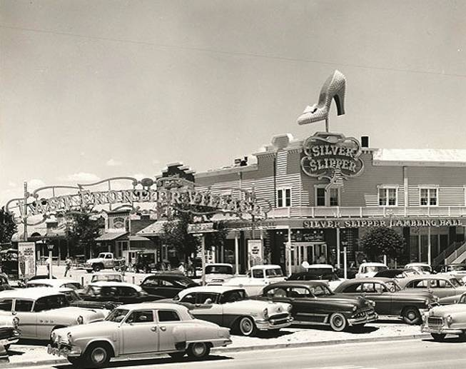 "Cars park outside the Silver Slipper Gambling Hall in this photo taken in the late 1950s to early '60s. Its original name is the Golden Slipper Gambling Hall and Saloon because ""Silver Slipper"" is unavailable at the time. It sits on the Last Frontier Village, right next to the Frontier Hotel."