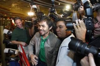 Manny Pacquiao makes his way through fans and media during his grand arrival at the MGM Grand Hotel on Tuesday. Pacquaio will face Miguel Cotto in a WBO welterweight title fight on Nov. 14 at the MGM Grand Garden Arena.