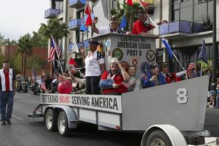 Veterans of the Las Vegas American Legion Post 8 salute to the crowd while riding in their float during the annual Veterans Day parade Wednesday in downtown Las Vegas.