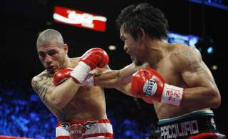 Miguel Cotto (L) takes a punch from Manny Pacquiao during their WBO welterweight title fight Saturday at the MGM Grand Garden Arena.