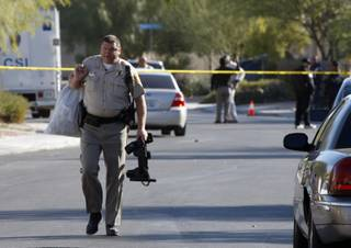 A Metro Police officer carries a bag and a police utility belt as he leaves the area of a crime scene and carries the items to a patrol car in North Las Vegas Thursday, Nov. 19, 2009.