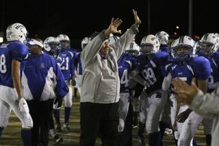 Basic assistant coach Dan Cahill celebrates with his team after a kickoff fumble recovery during the Sunrise Region semifinal game Friday night at Basic.  The Wolves were victorious over the Falcons 42-20.