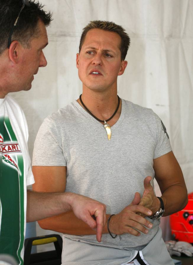 Seven-time Formula One World Driving Champion Michael Schumacher talks with a team member.