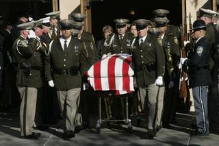 The body of Metro officer Trevor Nettleton is carried out of St. Elizabeth Ann Seton Church after funeral services Wednesday, November 25, 2009.
