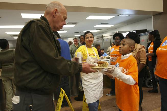 John Garrett, 8, stands first in line with volunteers handing trays of hot turkey dinners to those in need during the annual Thanksgiving community dinner at the Las Vegas Rescue Mission on Wednesday, Nov. 25, 2009.