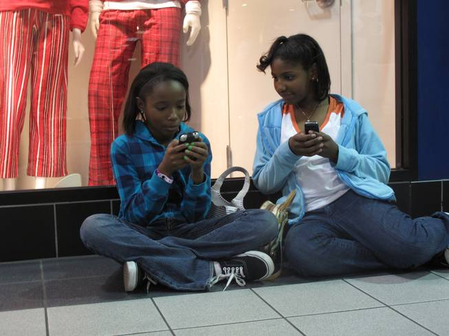 Kiani Talley, 12, and Brianna Robinson, 11, wait outside a ...
