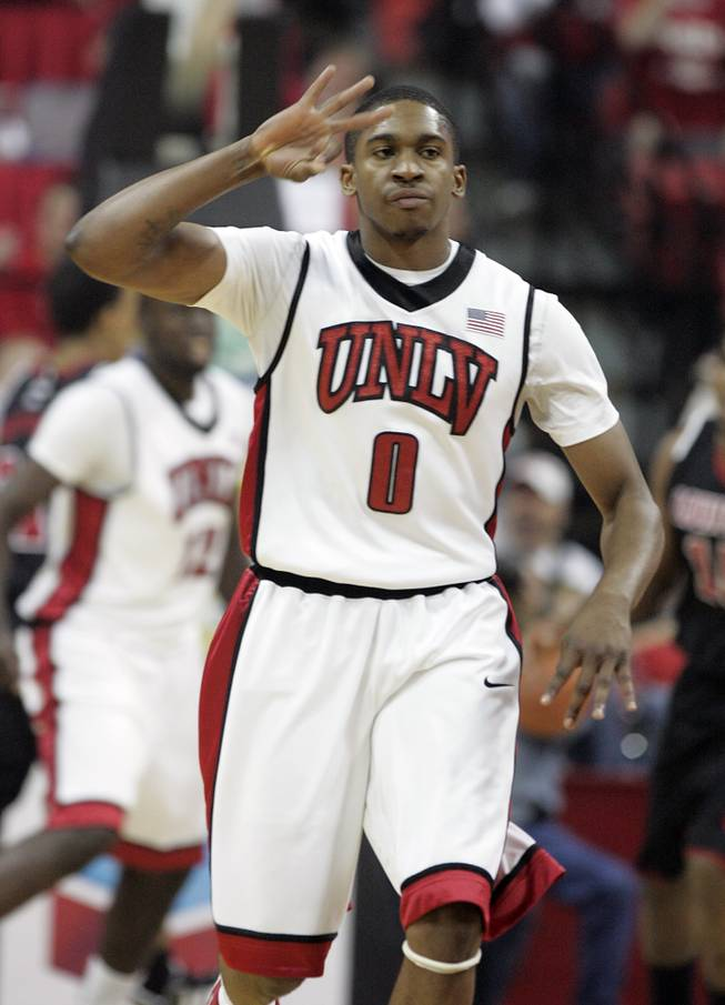 UNLV guard Oscar Bellfield signals sinking a 3-point shot against Louisville during the first half of a game on Nov. 28, 2009, at the Thomas & Mack Center. The Rebels upset the No. 16 Cardinals, 76-71.