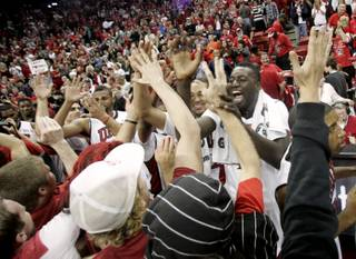 UNLV forward Brice Massamba and the rest of the Rebels celebrate their 76-71 upset of 16th-ranked Louisville Saturday at the Thomas & Mack Center.