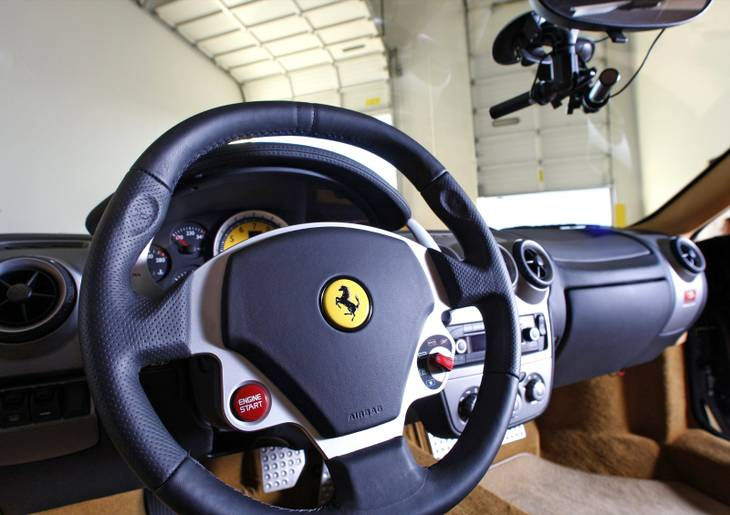 The interior of a 2007 Ferrari F430 F1 is displayed in the Exotics Racing warehouse at the Las Vegas Motor Speedway. Cameras, at top right, can record the road ahead.