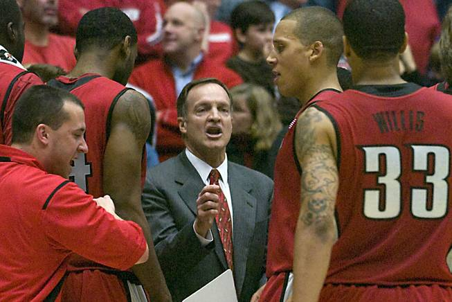 UNLV coach Lon Kruger, center, talks to his team during a during a second-half timeout against Arizona. UNLV won in double overtime, 74-72.