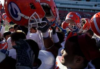 Members of the Bishop Gorman High football team hold their helmets in celebration Saturday following a 62-21 victory against Del Sol in the state championship game at Sam Boyd Stadium.