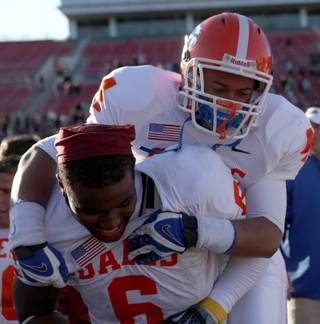 Bishop Gorman's Martin Tomaika jumps on the back of teammates Xavier Grimble Saturday in celebration of the Gaels 62-21 victory against Del Sol in the large-school state title game at Sam Boyd Stadium.